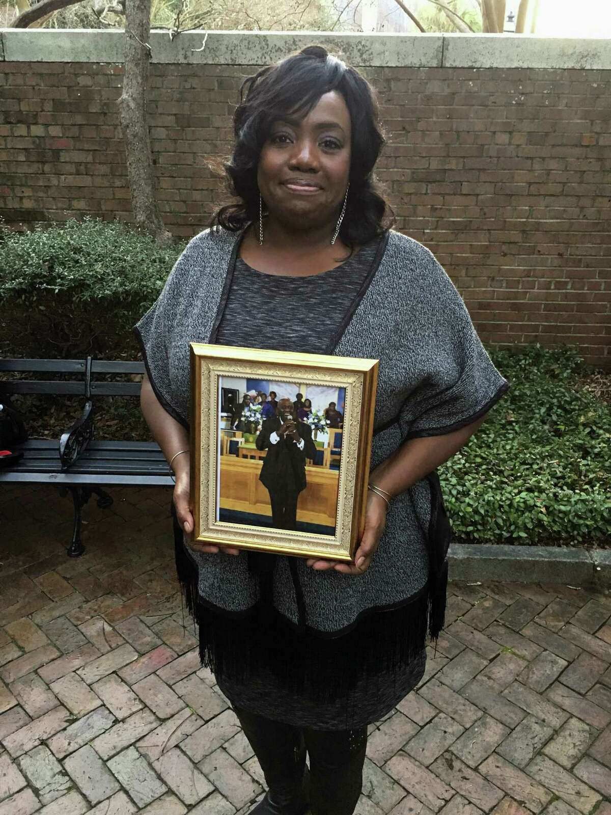 Rose Simmons, the daughter of Rev. Daniel Simmons, Sr., poses with a photograph of her father outside of U.S. District Court in Charleston, S.C. on Jan. 11, 2017, hours after Judge Richard Gergel formally confirmed jurors sentenced Dylann Roof to death. Simmons said Roof killed her father and eight others at Emanuel AME Church on June 17, 2015.