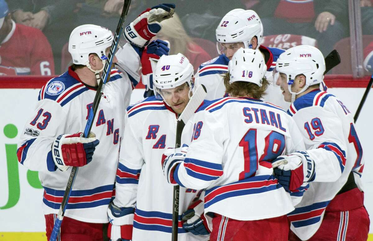 New York Rangers' Michael Grabner (40) is congratulated by teammates for his empty-net goal during third period against the Montreal Canadiens in Game 1 of an NHL first-round hockey playoff series Wednesday in Montreal.
