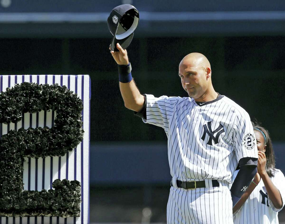 In this Sept. 7, 2014 photo, New York Yankees' Derek Jeter (2) tips his cap to fans during a pregame ceremony honoring the Yankees captain. Jeter wrote an essay published May 11, 2017 on his Players' Tribune site thanking the city before his No. 2 jersey is permanently retired by the team on May 14.