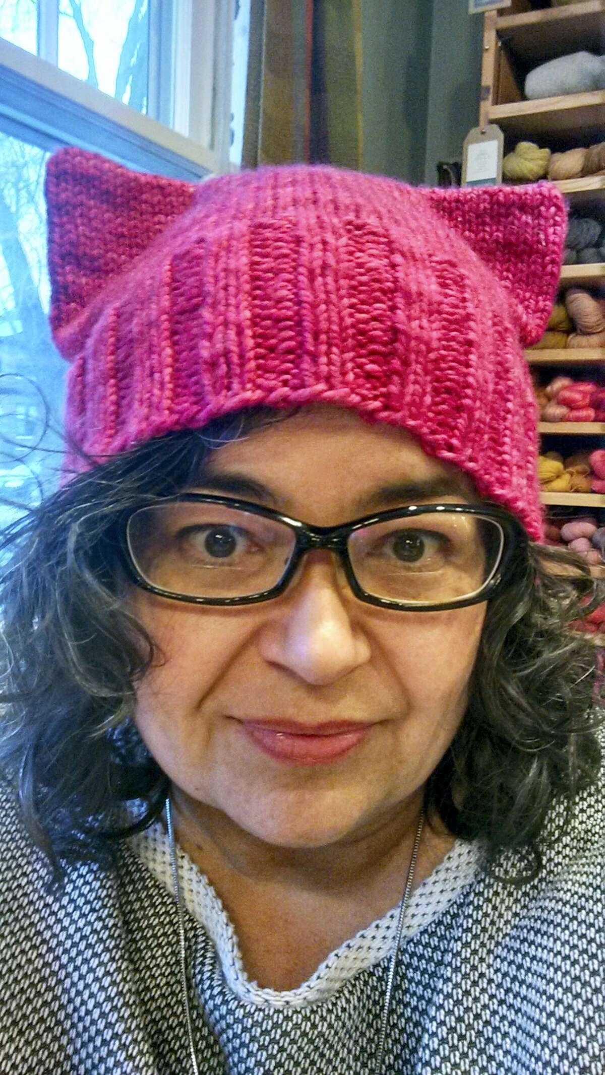 """This January 2017 photo provided by Angie Paulson, shows Paulson, a knitter who works at The Yarnery shop in Saint Paul, Minn., as she displays one of the """"pussy"""" hats she made as part of a call to action answered by thousands of knitters to supply marchers at the Women's March in Washington, D.C., on Jan. 21 with warm head gear and a way to show their solidarity for women's rights."""
