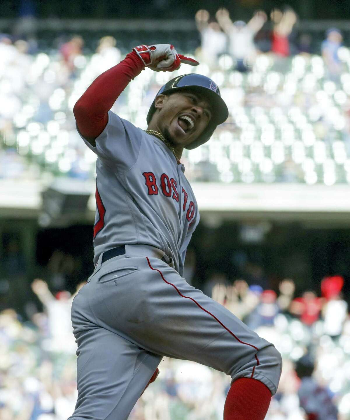 Mookie Betts reacts as he rounds first after hitting a home run in the ninth inning.