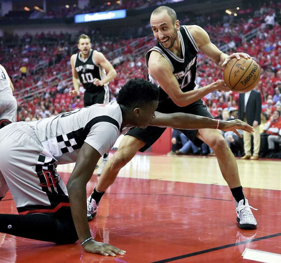 Spurs guard Manu Ginobili, right, grabs a loose ball from Rockets center Clint Capela during the first half Thursday. Photo: Eric Christian Smith — The Associated Press  / FR171023 AP