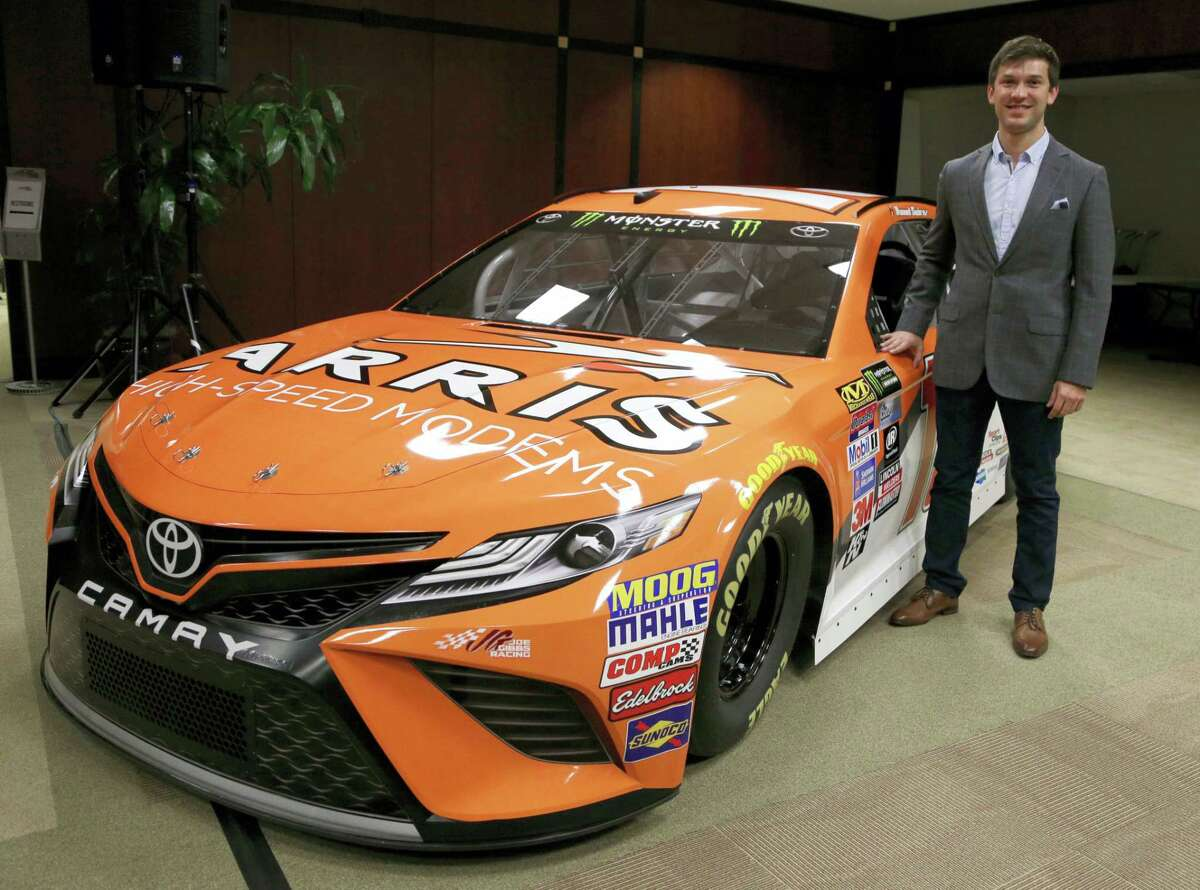 Driver Daniel Suarez poses for a photo with the NASCAR Cup Series race car he will drive this season during a news conference at Joe Gibbs Racing in Huntersville, N.C. on Wednesday. Suarez is replacing Carl Edwards who announced Wednesday he is stepping away from racing.