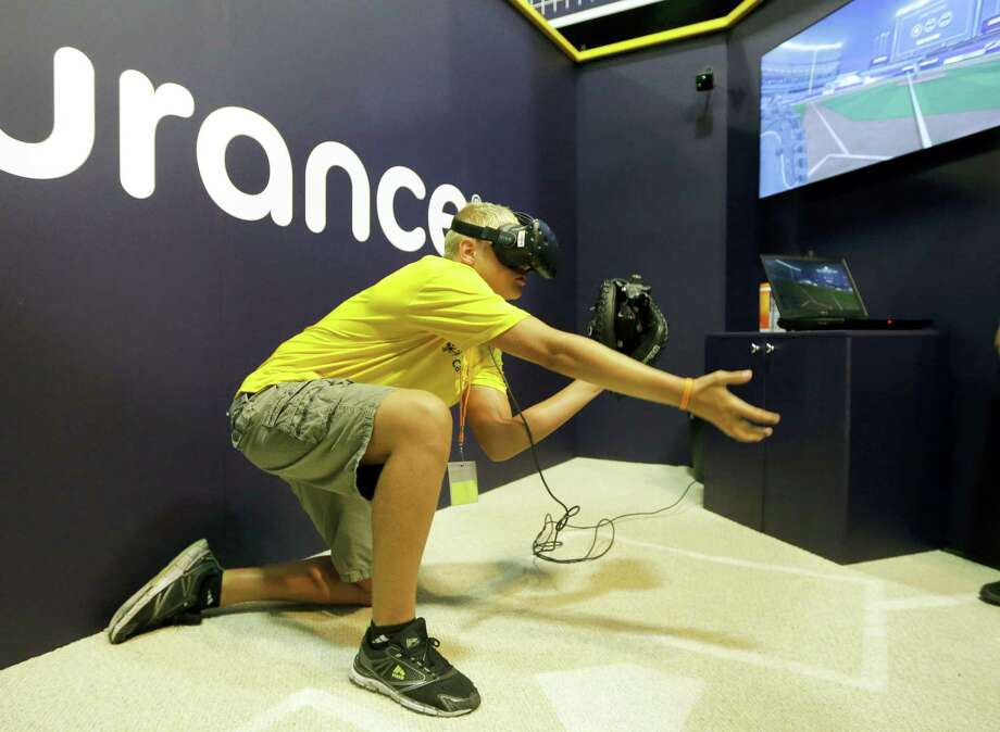 Dennis Milman reaches to catch a virtual ball at the All-Star FanFest in Miami Beach, Fla. Photo: The Associated Press File Photo  / Copyright 2017 The Associated Press. All rights reserved.