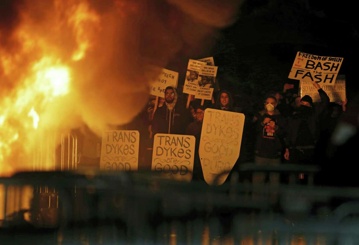 Protestors watch a fire on Sproul Plaza during a rally against the scheduled speaking appearance by Breitbart News editor Milo Yiannopoulos on the University of California at Berkeley campus on Wednesday, Feb. 1, 2017, in Berkeley, Calif. The event was canceled out of safety concerns after protesters hurled smoke bombs, broke windows and started a fire.