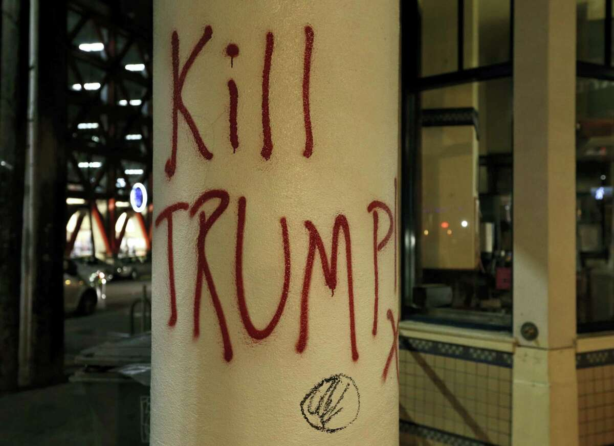 Graffiti left by protesters who were against a scheduled speaking appearance by Breitbart News editor Milo Yiannopoulos is seen Wednesday, Feb. 1, 2017, in Berkeley, Calif. A small group of people with their faces covered broke windows, hurled fireworks at police officers and threw smoke bombs, prompting UC Berkeley officials to cancel Yiannopoulos's talk Wednesday evening.