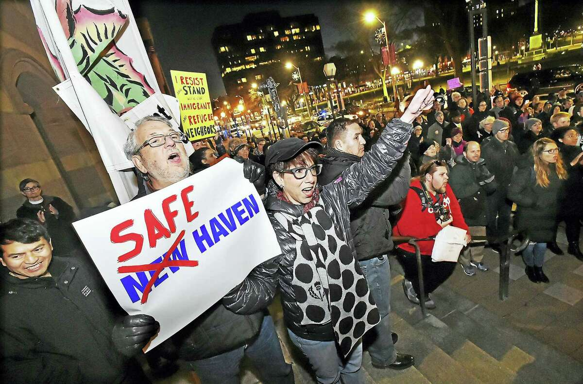 """Hamden residents Tim and Diane Nighswander hold a sign, """"Safe Haven"""" during a rally at New Haven City Hall protesting President Donald J. Trump's policies on immigration and sanctuary cities Jan. 26. New Haven has declared itself a safe haven for immigrants."""