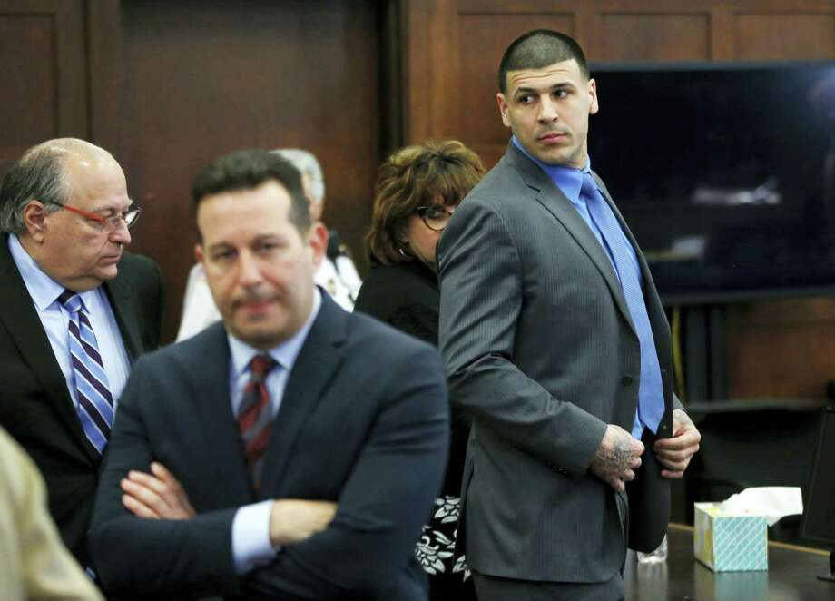 Defendant Aaron Hernandez, right, stands and looks as his attorneys confer during his double murder trial at Suffolk Superior Court, Tuesday, April 11, 2017, in Boston. Hernandez is on trial for the July 2012 killings of Daniel de Abreu and Safiro Furtado who he encountered in a Boston nightclub. The former New England Patriots NFL player is already serving a life sentence in the 2013 killing of semi-professional football player Odin Lloyd. Photo: AP Photo/Elise Amendola, Pool   / Pool AP