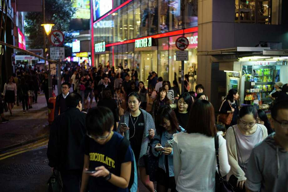 Pedestrians at night in the Causeway Bay district of Hong Kong, China on April 14, 2016. Photo: Bloomberg Photo By Billy H.C. Kwok  / © 2016 Bloomberg Finance LP