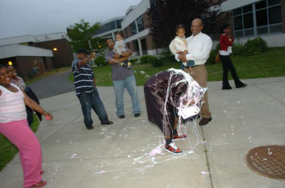 Kevin Vereen tries to avoid a silly string attack by his family after graduating at Bridge Academy's 13th Annual Commencement Exercises held at Thurgood Marshall Middle School in Bridgeport, Conn. on Wednesday evening June 16, 2010. It was also Kevin's birthday. Photo: Christian Abraham / Connecticut Post