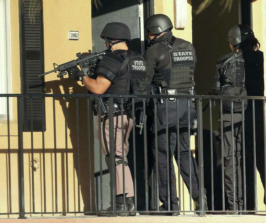 Law enforcement officers conduct a door-to-door search at an apartment complex in Orlando, Fla. on Jan. 9, 2017. An Orlando police sergeant was shot and killed Monday after approaching a suspect wanted for questioning in the murder of his pregnant ex-girlfriend, and a second law enforcement officer was killed in a motorcycle crash while responding to the massive manhunt for the suspect. Photo: Stephen M. Dowell/Orlando Sentinel Via AP  / Orlando Sentinel 2016