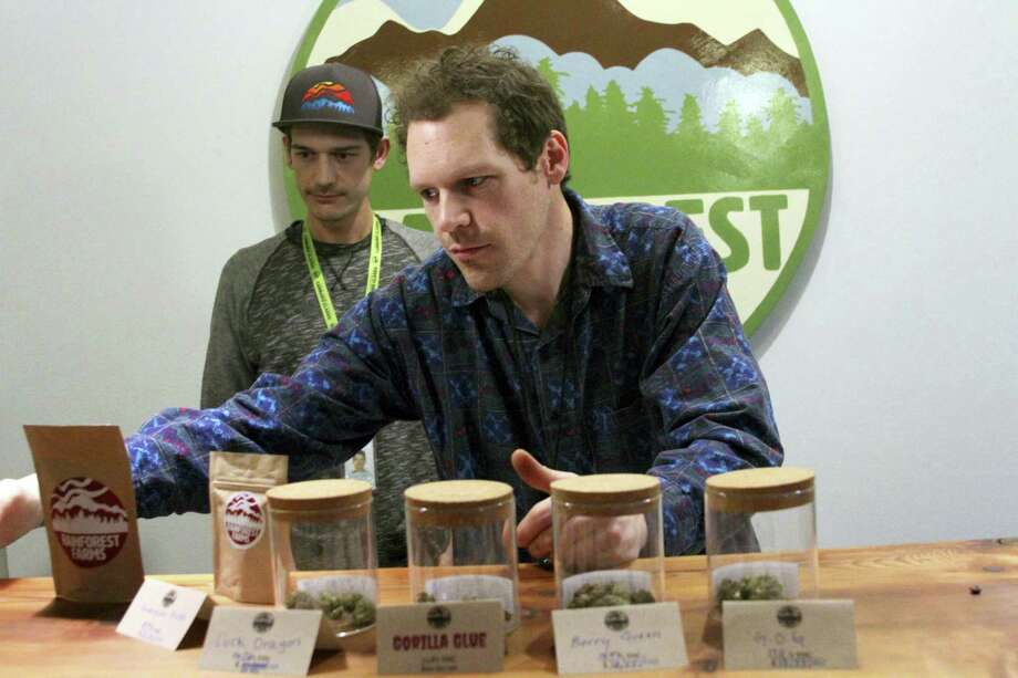 Giono Barrett, right, arranges marijuana products at Rainforest Farms in Juneau, Alaska. James Barrett, left, is co-owner of Juneau's first marijuana retail store. James and Giono Barrett have a dream: that some of the scores of cruise ship passengers who crowd the streets of the state capital each summer will one day use their shore excursions to kick back and light up a joint in a pot store's lounge. Photo: Mark Thiessen — AP Photo  / Copyright 2017 The Associated Press. All rights reserved. This material may not be published, broadcast, rewritten or redistribu