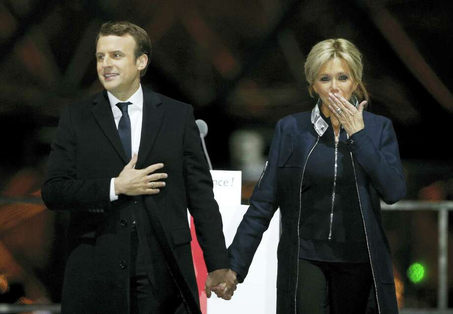 "French President-elect Emmanuel Macron holds hands with his wife Brigitte during a victory celebration outside the Louvre museum in Paris, France. Speaking to thousands of supporters from the Louvre Museum's courtyard, Macron said that France is facing an ""immense task"" to rebuild European unity, fix the economy and ensure security against extremist threats. Photo: Thibault Camus — The Associated Press  / Copyright 2017 The Associated Press. All rights reserved."