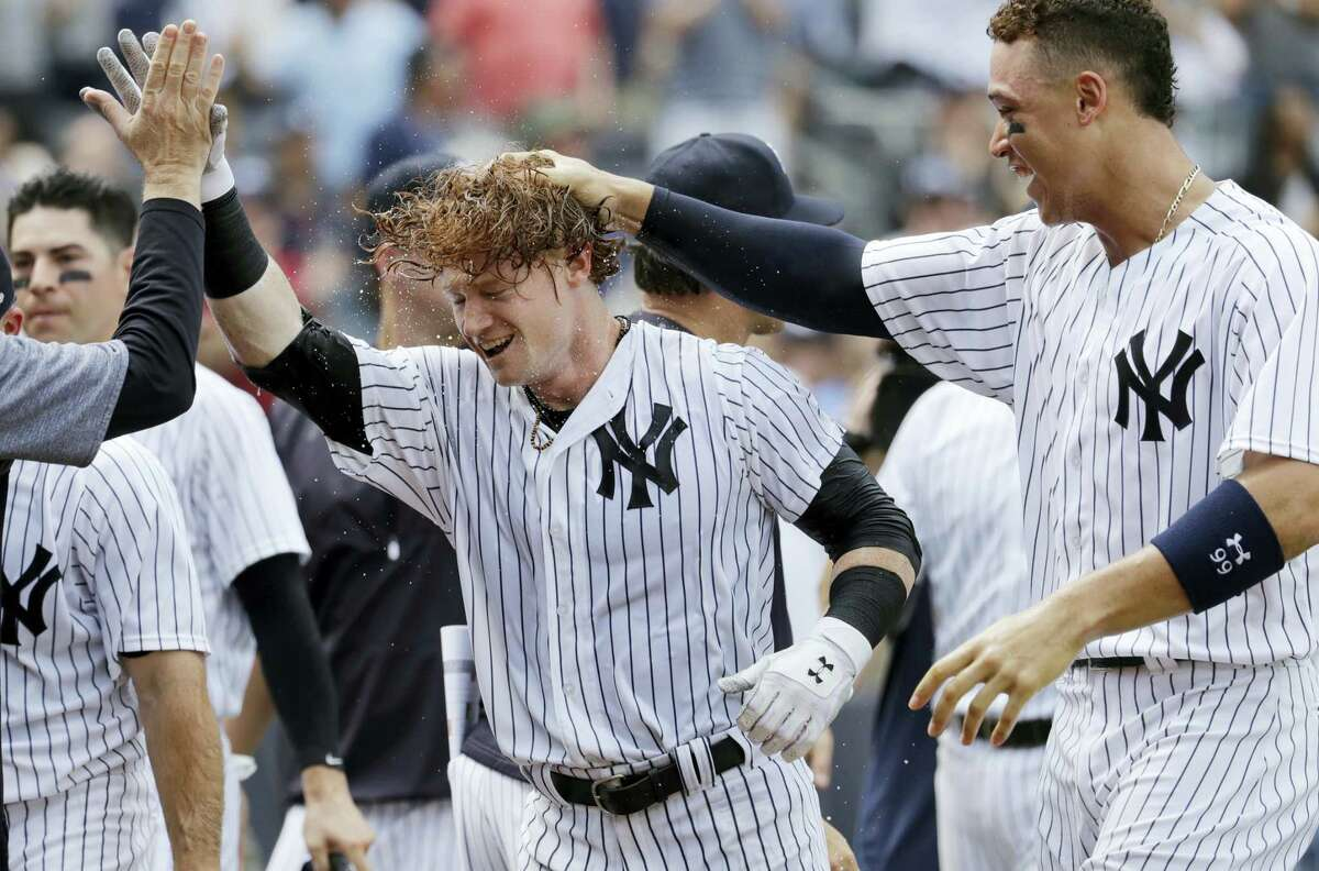 The Yankees' Clint Frazier, center, is congratulated by teammates after hitting a three-run walk-off home run during the ninth inning against the Brewers Saturday at Yankee Stadium.