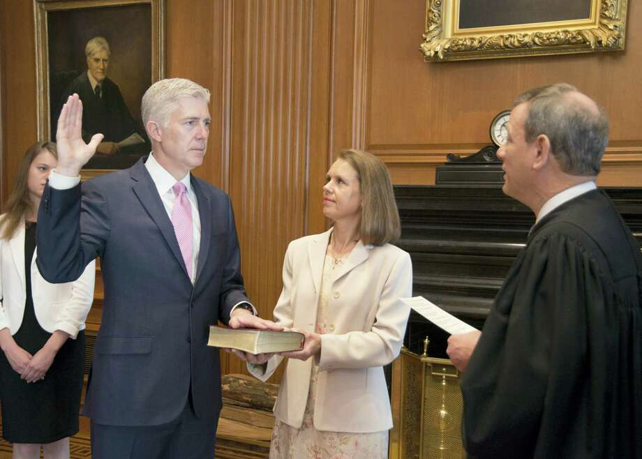 In this photo provided by the Public Information Office Supreme Court of the U.S. Chief Justice John G. Roberts, Jr., administers the Constitutional Oath to the Neil Gorsuch in a private ceremony attended by the Justices of the Supreme Court and members of the Gorsuch family, including wife Louise Gorsuch on April 10, 2017, in the Justices' Conference Room at the Supreme Court in Washington. Surrounded by family and his soon-to-be Supreme Court colleagues, Gorsuch took the first of two oaths as he prepared to take his seat on the court. Photo: Franz Jantzen — Public Information Office Supreme Court Of The U.S. Via AP  / Franz Jantzen, Collection of the Supreme Court of the United States