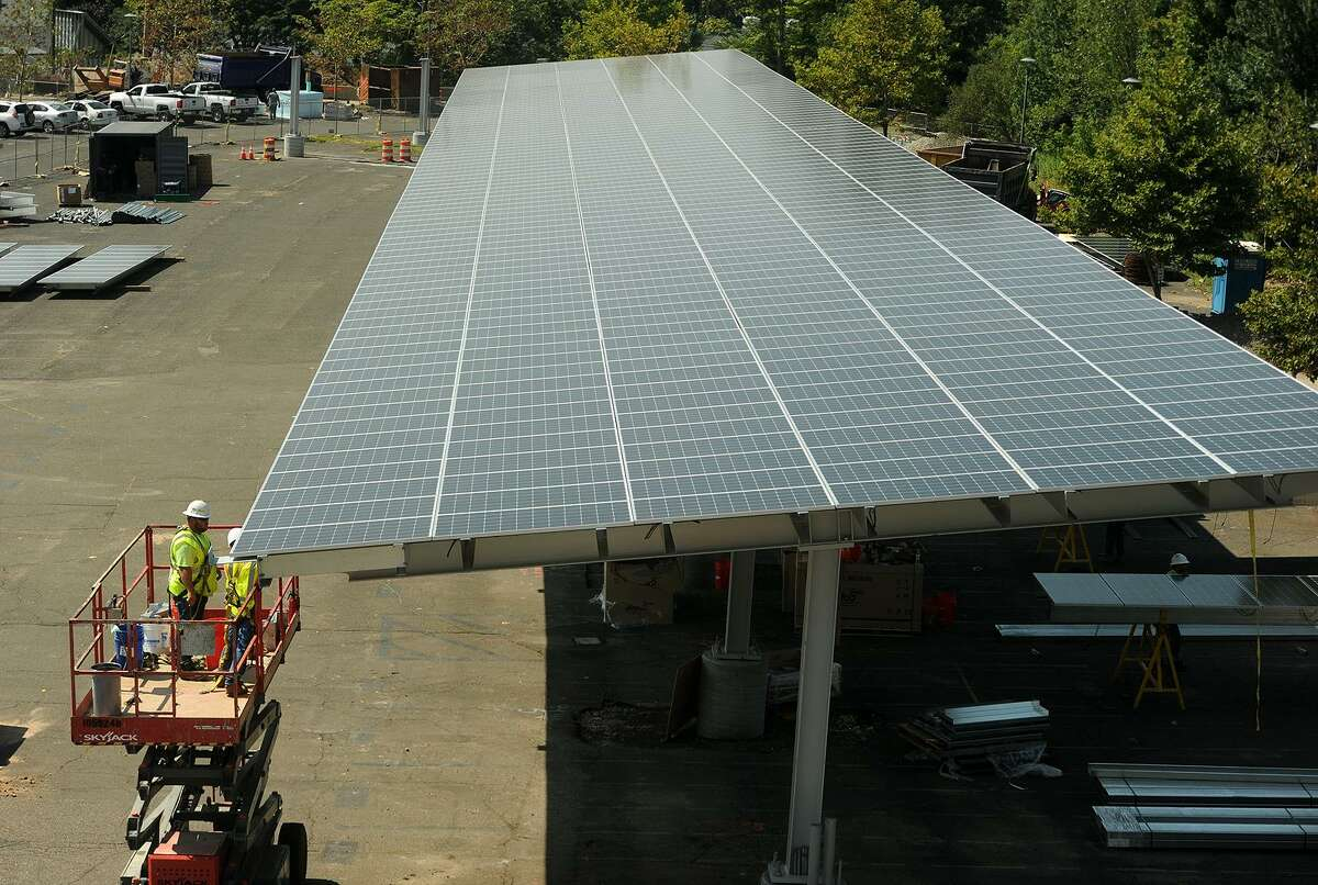 Workers install massive solar power iarrays above the student parking lot at Fairfield Ludlowe High School in Fairfield, Conn. on Thursday, August 10, 2017. An identical project is being undertaken at Fairfield Warde High School.