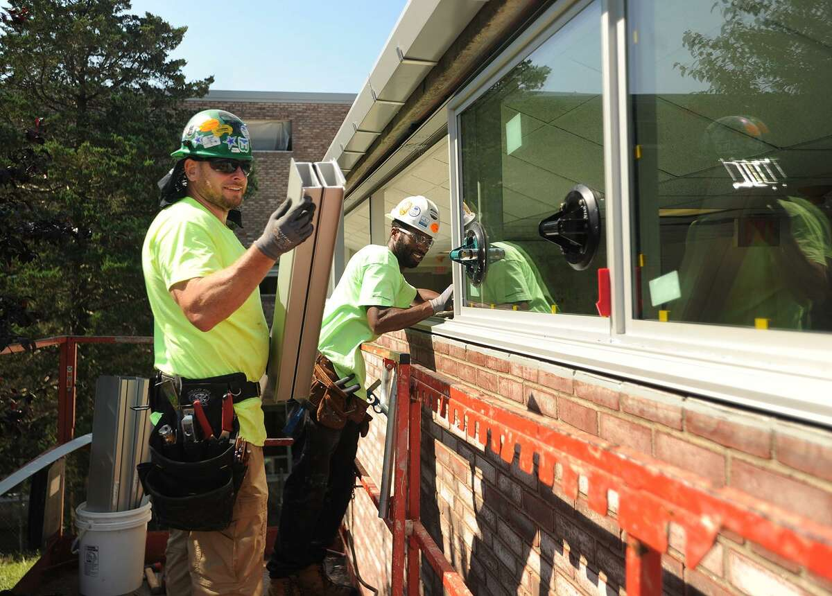 Robert Fix, left, of Hartford, and John Bennett, of New Haven, employees of Cherry Hill Glass, of Branford, install new windows at Fairfield Ludlowe High School in Fairfield, Conn. on Thursday, August 10, 2017.