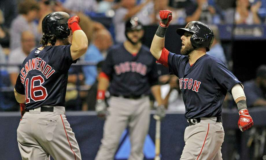 Andrew Benintendi, left, celebrates with Dustin Pedroia after scoring on Pedroia's two-run home run in the third inning Friday in St. Petersburg, Fla. Photo: Steve Nesius — The Associated Press  / FR69810 AP