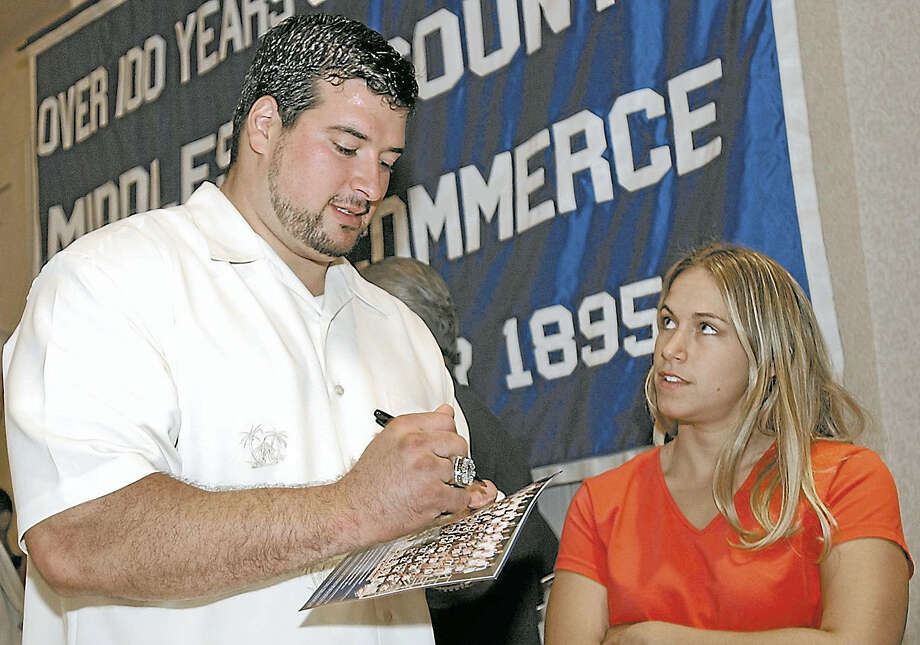 New England Patriots football player Joe Andruzzi autographs a photo of the team after the Middlesex Chamber of Commerce breakfast on June 18, 2002. Photo: Middletown Press File Photo