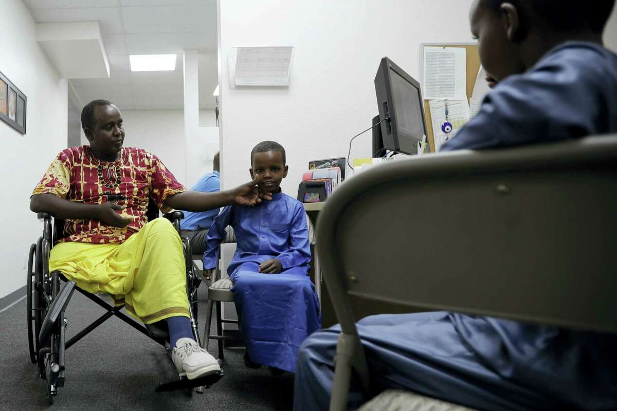 Ali Said, of Somalia, left, waits at a center for refugees with his two sons Thursday, July 6, 2017, in San Diego. Said, whose leg was blown off by a grenade, says he feels unbelievably lucky to be among the last refugees allowed into the United States before stricter rules kick in as part of the Trump administration's travel ban.