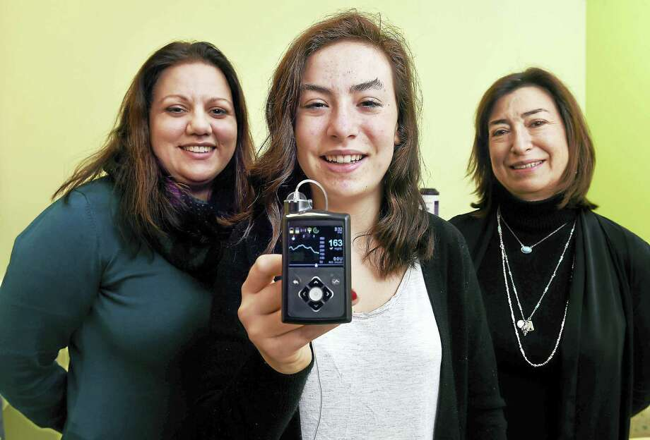 Claire Bickel, center, 14, of Branford holds a monitor that is part of the Medtronic MiniMed670G insulin pump system. With her are her pediatric endocrinologist, Dr. Jennifer Sherr, left, and mother, Francesca Bickel, at the Pediatric Specialty Center in New Haven. The display shows her blood sugar level. Photo: Arnold Gold — New Haven Register