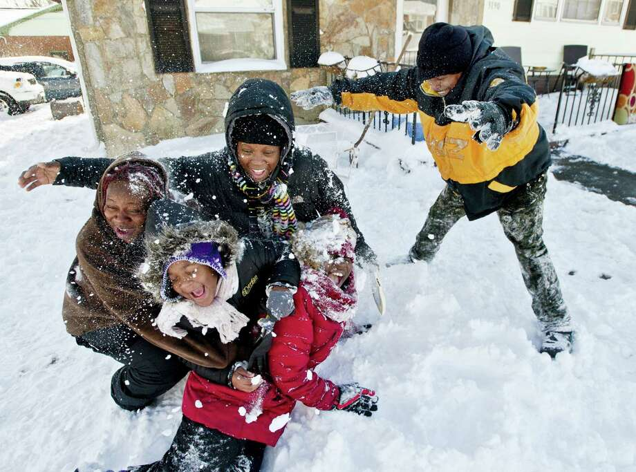 Barry Boykin throws snow on his neighbors Larniece Clemmons, from left, Taylor Porter, 7, Shondell Porter, and Jaynea Smith, 9, as they play along Carver School Road, after 6-8 inches of snow fell across the Triad on Jan. 7, 2017 in Winston-Salem, N.C. Photo: Walt Unks/The Winston-Salem Journal Via AP  / The Winston-Salem Journal