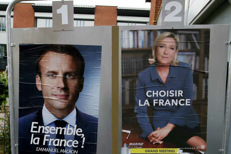 Election campaign posters for French centrist presidential candidate Emmanuel Macron and far-right candidate Marine Le Pen are displayed in front of the polling station where Marine Le Pen will vote in Henin Beaumont, northern France on Saturday, May 6, 2017. Voting for France's next president starts in overseas territories and French embassies abroad, as a blackout on campaigning descends so that voters can reflect on whether to entrust their country's future to independent Emmanuel Macron or far-right populist Marine Le Pen. Photo: AP Photo — Francois Mori  / AP