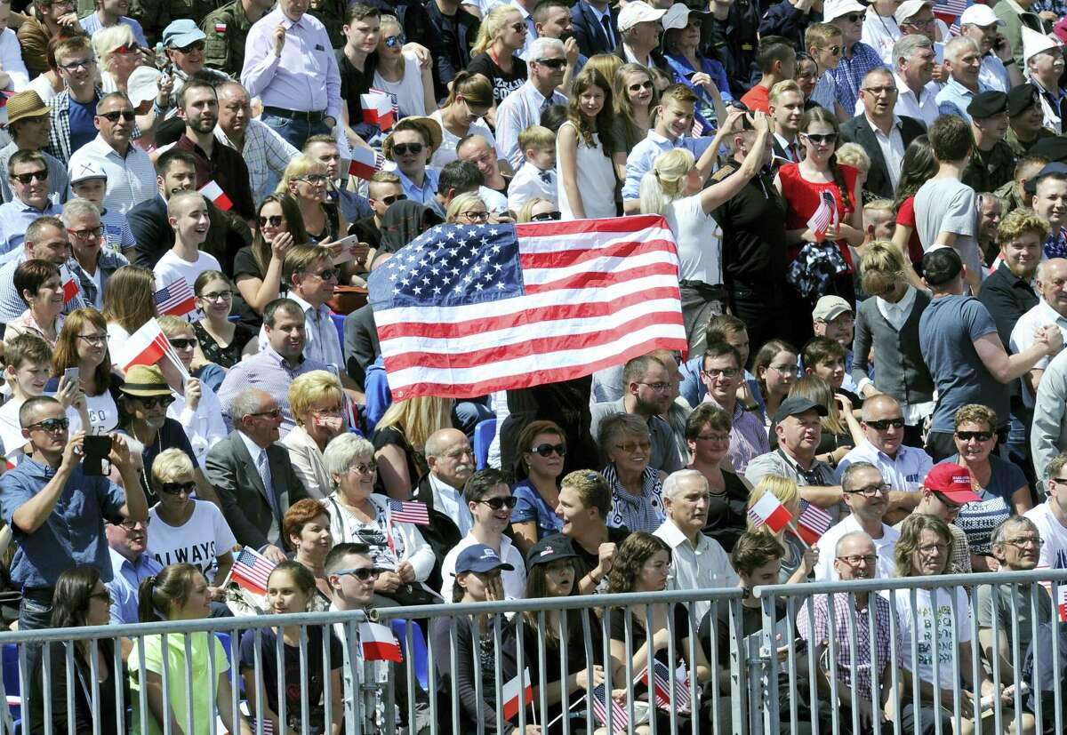 Poles hold a Unites States flag while waiting for U.S. President Donald Trump to deliver a speech in Krasinski Square, in Warsaw, Poland, Thursday, July 6, 2017.