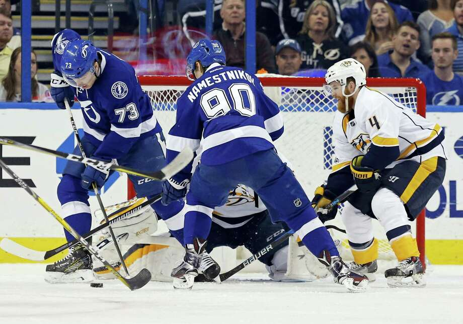 The Lightning's Adam Erne (73) looks for a puck in front of Nashville Predators goalie Pekka Rinne during their game on Thursday. Photo: The Associated Press   / FR155492 AP
