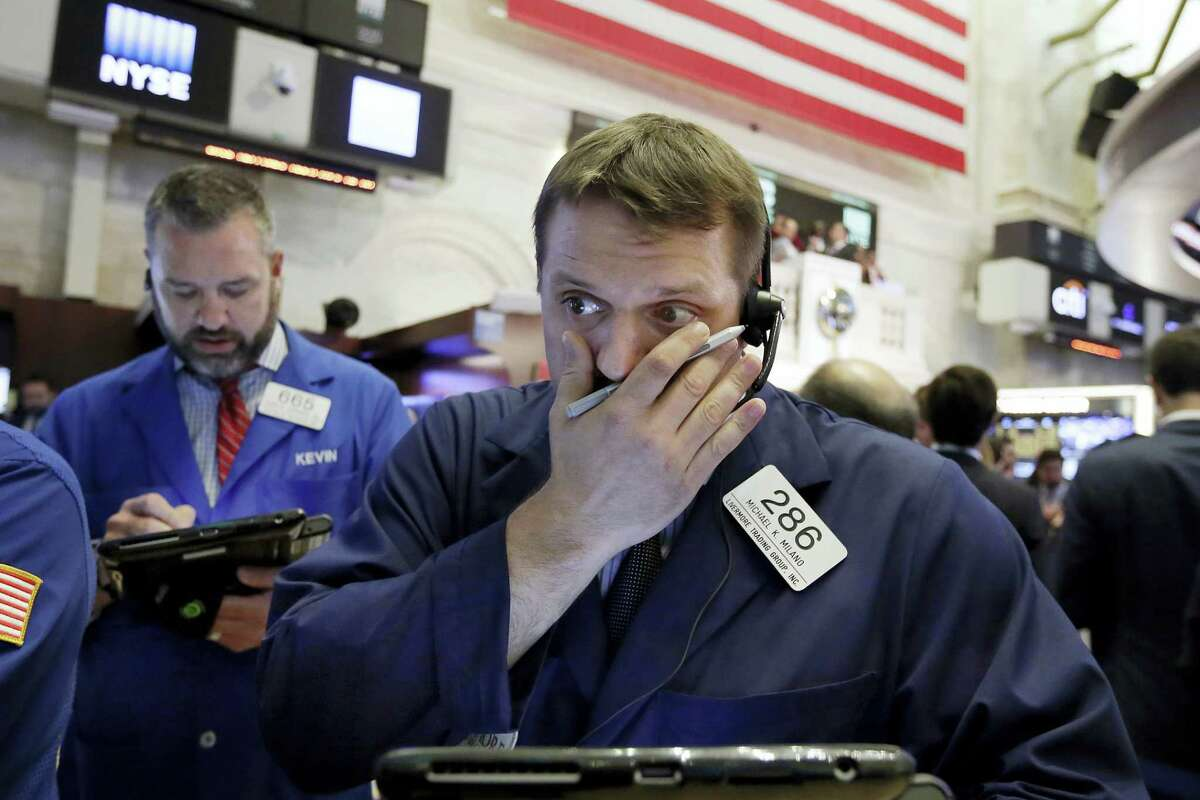 Traders Michael Milano, right, and Kevin Lodewick work on the floor of the New York Stock Exchange Thursday.