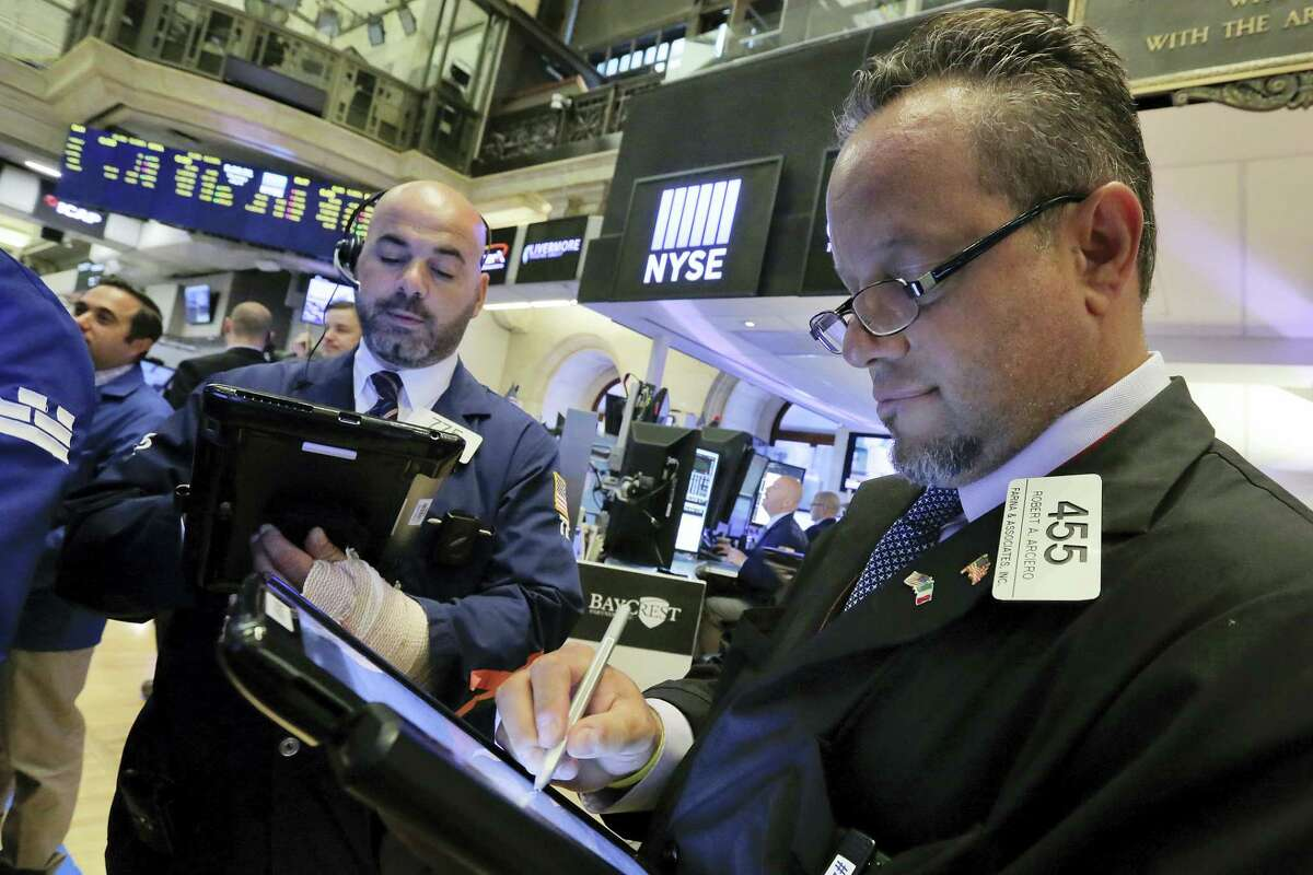 Traders Fred DeMarco, left, and Robert Arciero work on the floor of the New York Stock Exchange Thursday.