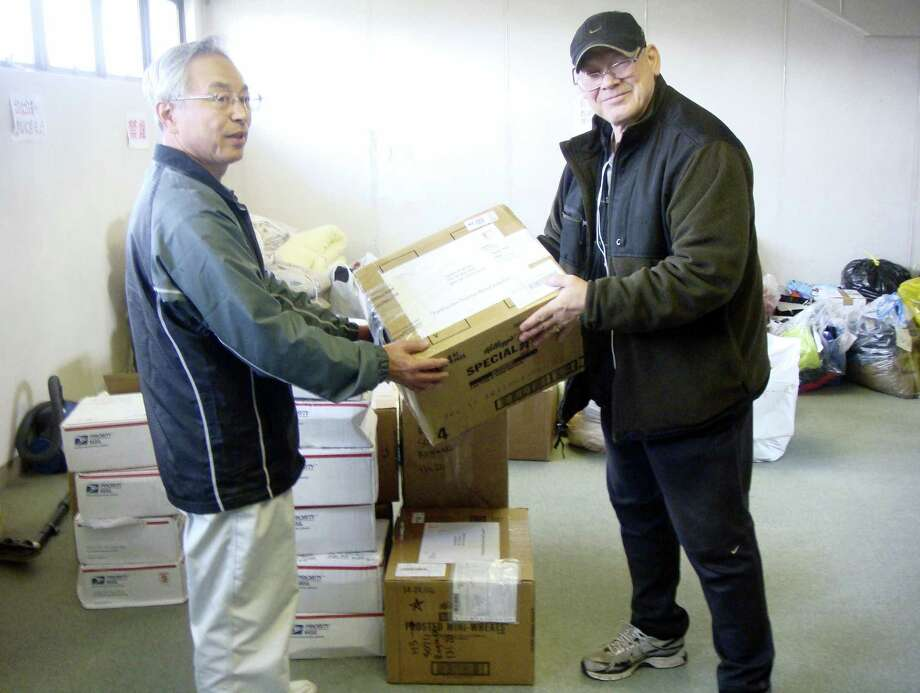 Joseph Roginski, right, holds a package in a storeroom of the Misawa City Hall in Japan, where donations of clothing and supplies were being kept for earthquake relief efforts. He says that while the cost of living is higher in Japan, access to health care is not. Photo: Joseph Roginski Via AP  / Joseph Roginski