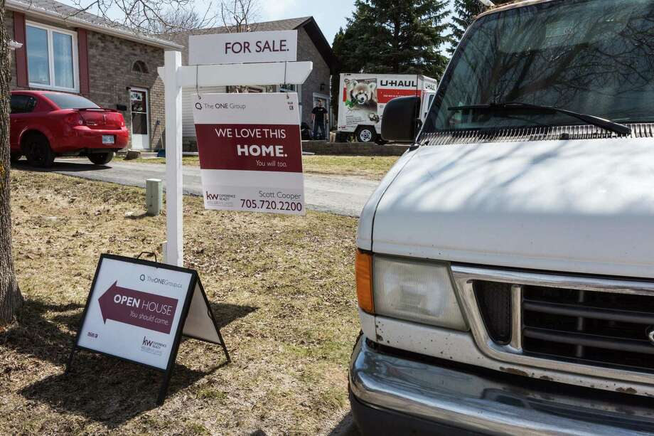"""A """"For Sale"""" sign stands on display outside an open house in Barrie, Ontario. Photo: Mark Sommerfeld — Bloomberg  / © 2017 Bloomberg Finance LP"""