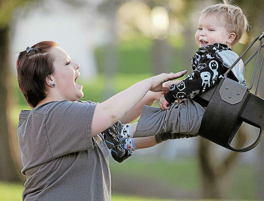 A mother pushes her 2-year-old son on the swing at Butternut Hollow Park in this archive photograph. Photo: File Photo  / TheMiddletownPress