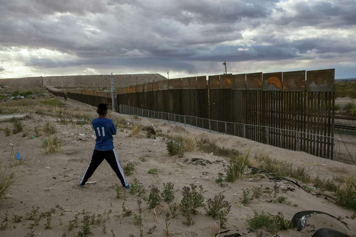 In this March 29, 2017 photo, a youth looks at a new, taller fence being built along U.S.-Mexico border, replacing the shorter, gray metal fence in front of it, in the Anapra neighborhood of Ciudad Juarez, Mexico, across the border from Sunland Park, New Mexico. Most Americans oppose funding President Donald Trump's wall along the U.S.-Mexico border. That's according to a poll released Thursday by The Associated Press-NORC Center for Public Affairs Research.