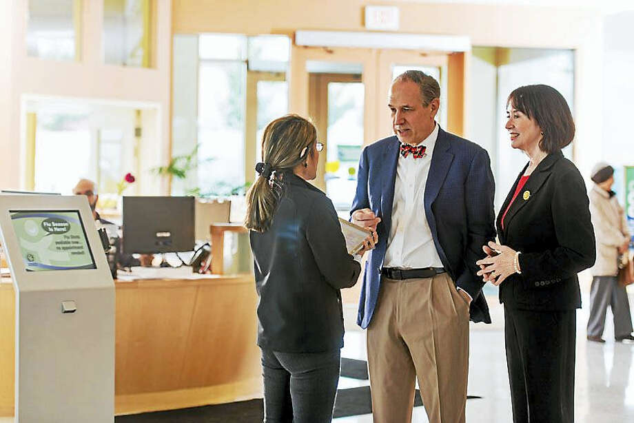 Community Health Center cofounder and CEO Mark Masselli, center, and CHC Senior VP and Clinical Director Dr. Margaret Flinter, right, speak to an employee in the Middletown office. Photo: Michael Lee-Murphy — Connecticut Magazine