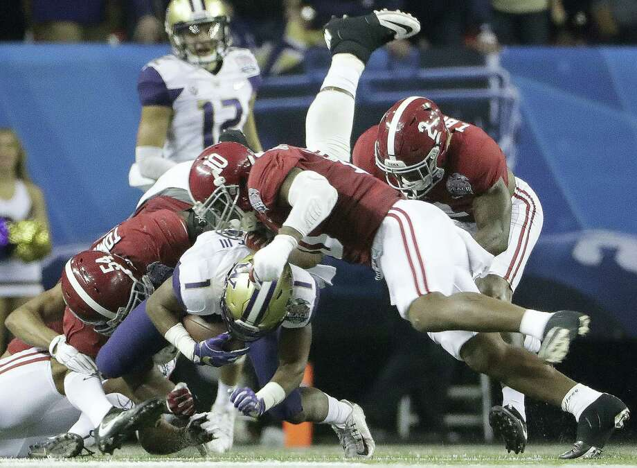 Washington wide receiver John Ross (1) is tackled by Alabama defensive lineman Dalvin Tomlinson (54) and Alabama linebacker Reuben Foster (10) during the first half of the Peach Bowl. Photo: David Goldman — The Associated Press  / Copyright 2016 The Associated Press. All rights reserved.