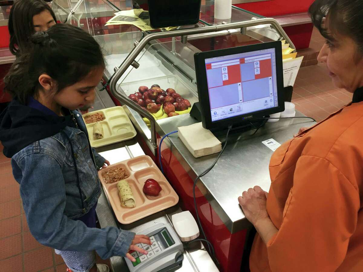 In this Thursday, May 4, 2017 photo, third grader Elliana Vigil punches in his student identification meal to pay for a meal at Gonzales Community School in Santa Fe, N.M. All students are offered the same lunch at Gonzales and other Santa Fe public schools to avoid any chance of embarrassing students whose parents may have fallen behind on meal payments. New Mexico in April became the first state to outlaw the shaming of children for any unpaid meals.