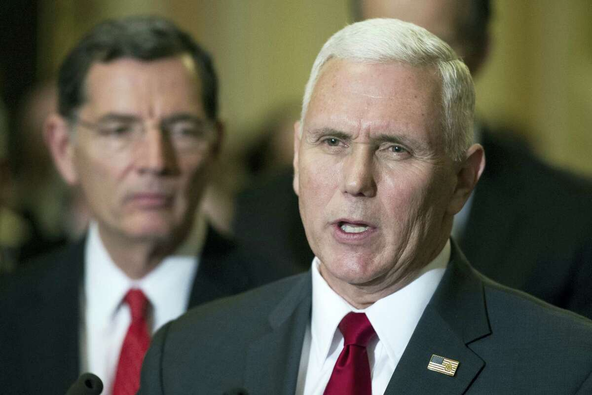 Vice President-elect Mike Pence speaks with reporters on Capitol Hill in Washington on Jan. 4, 2017 after attending a Senate Republican Luncheon. Sen. John Barrasso, R-Wyo. listens at left.