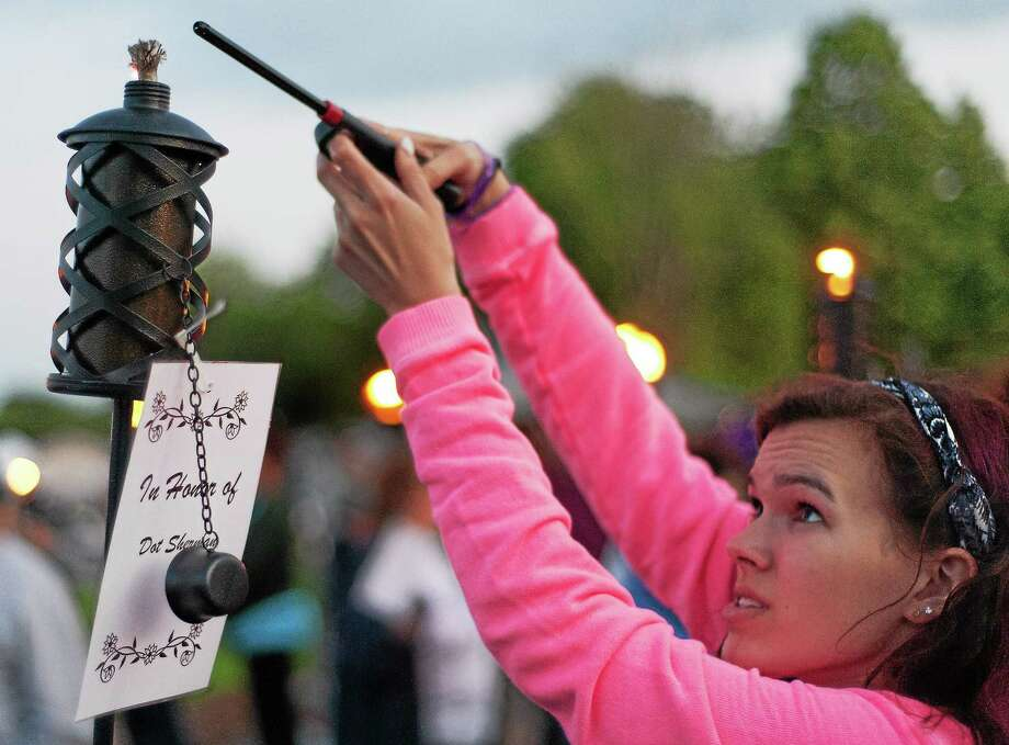 A participant in the 2014 Greater Middletown Relay for Life lights a candle in honor of Dot Sherman at Woodrow Wilson Middle School. This year's event at the high school runs for 24 hours at the end of June. Photo: File Photo  / RAY SHAW