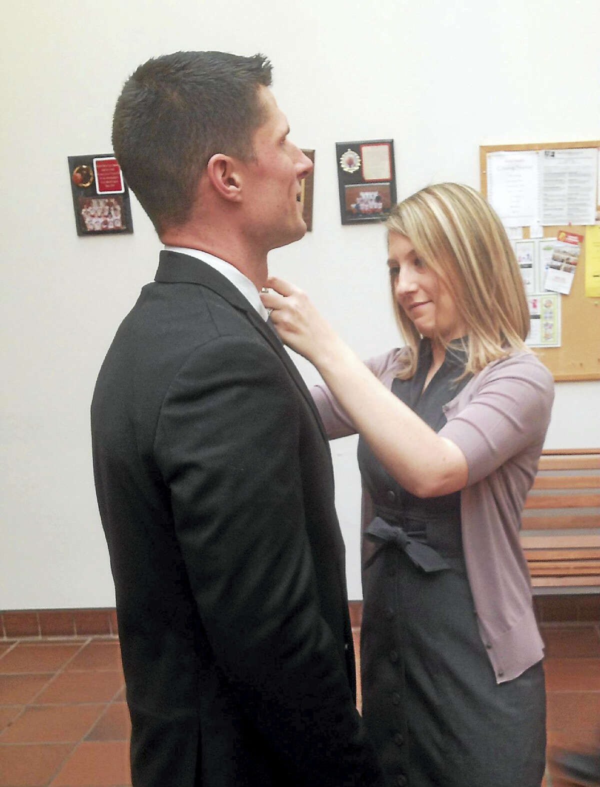 Jeff Mill —The Middletown Press Jennifer Wobrock pins the badge of her husband, Cromwell Police Officer Ryan Wobrock, on his uniform Monday morning at police headquarters.