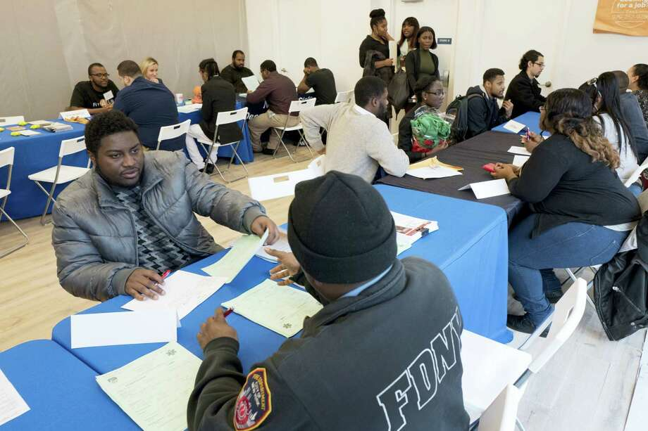 In this Nov. 15, 2016 photo, Kenneth Bennett, left, talks with a recruiter from the Fire Department City of New York during a job fair hosted by the Gregory Jackson Center for Brownsville, in the Brooklyn borough of New York. On May 4, 2017, the Labor Department reports on the number of people who applied for unemployment benefits a week earlier. Photo: AP Photo — Mark Lennihan  / Copyright 2017 The Associated Press. All rights reserved.
