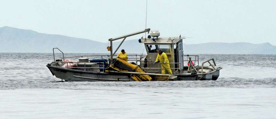 Crews recover boom a boom used in oil recovery operations after a spill in the Santa Barbara Channel off Refugio State Beach in Goleta, Calif. on May 21, 2015. Photo: Petty Officer 3rd Class Andrea Anderson — U.S. Coast Guard Via AP  / U.S. Coast Guard