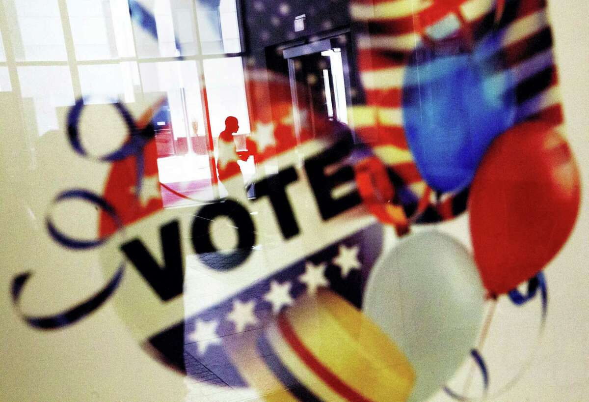 In this Nov. 1, 2016, photo, a voter is reflected in the glass frame of a poster while leaving a polling site in Atlanta, during early voting ahead of the Nov. 8 election day. If all goes smoothly, the American people will choose a new president on Tuesday, the Electoral College will affirm the election and either Democrat Hillary Clinton or Republican Donald Trump will take the oath of office Jan. 20.