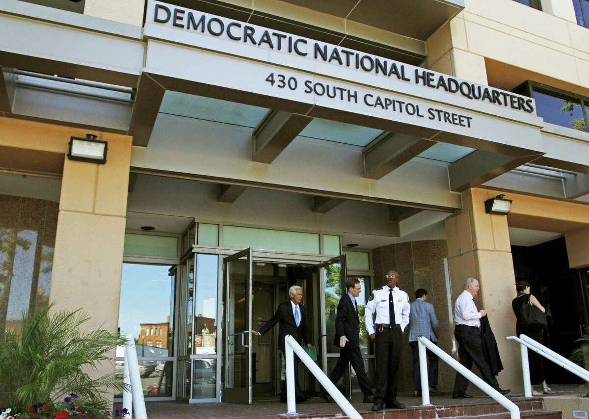 In this June 14, 2016, file photo, people stand outside the Democratic National Committee (DNC) headquarters in Washington. The U.S. has released its most detailed report yet on accusations that Russia interfered in the U.S. presidential election by hacking American political sites and email accounts. The 13-page joint analysis by the Department of Homeland Security and the FBI is the first such report ever to attribute malicious cyber activity to a particular country or actors.