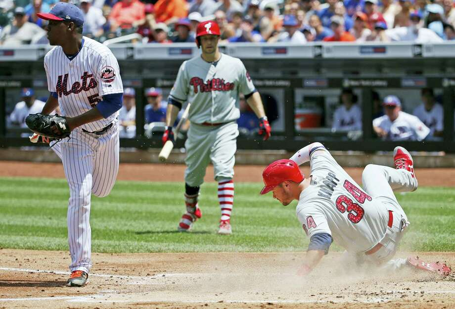 A batboy, center, watches as the Phillies' Andrew Knapp (34) scores on a wild pitch Mets starter Rafael Montero, left, during the second inning Sunday. Photo: Kathy Willens — The Associated Press  / Copyright 2017 The Associated Press. All rights reserved.
