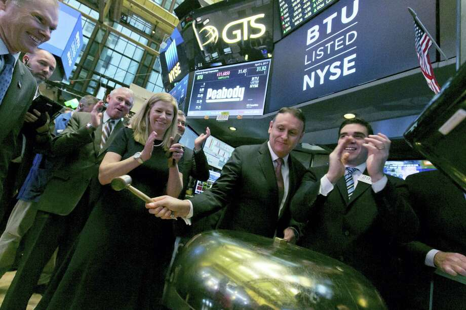 Peabody Energy Corp. President & CEO Glenn Kellow, second from right, joined by company CFO Amy Schwetz, rings a ceremonial bell as his company's stock begins trading on the floor of the New York Stock Exchange Tuesday. The nation's largest coal producer, Peabody Energy Corp., said Monday that it has emerged from bankruptcy protection after a year. The St. Louis company said it reduced costs and slashed its debt load by more than $5 billion in the past year. Photo: Richard Drew — The Associated Press  / AP