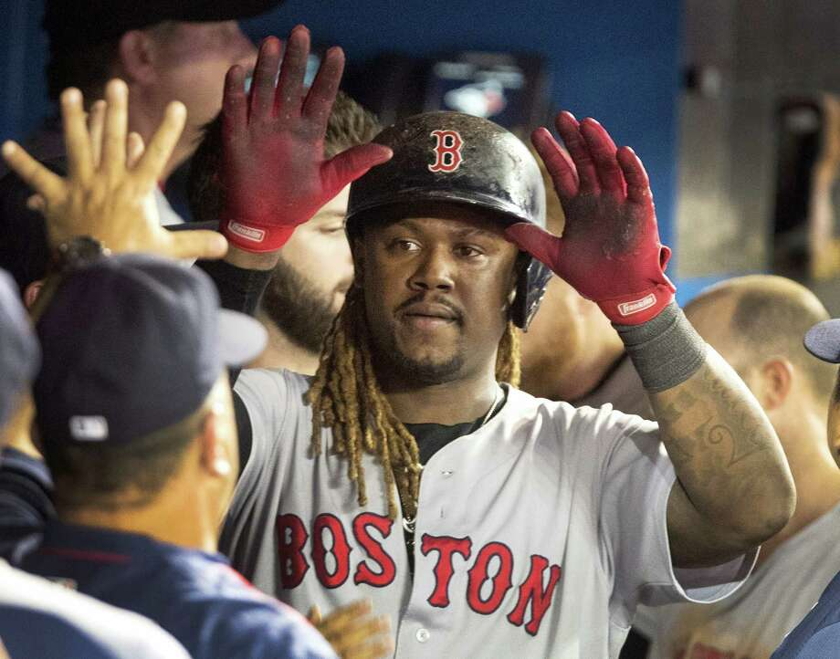 Hanley Ramirez gets high-fives in the dugout after scoring the go-ahead run during the 11th inning. Photo: Fred Thornhill — The Canadian Press Via AP  / The Canadian Press