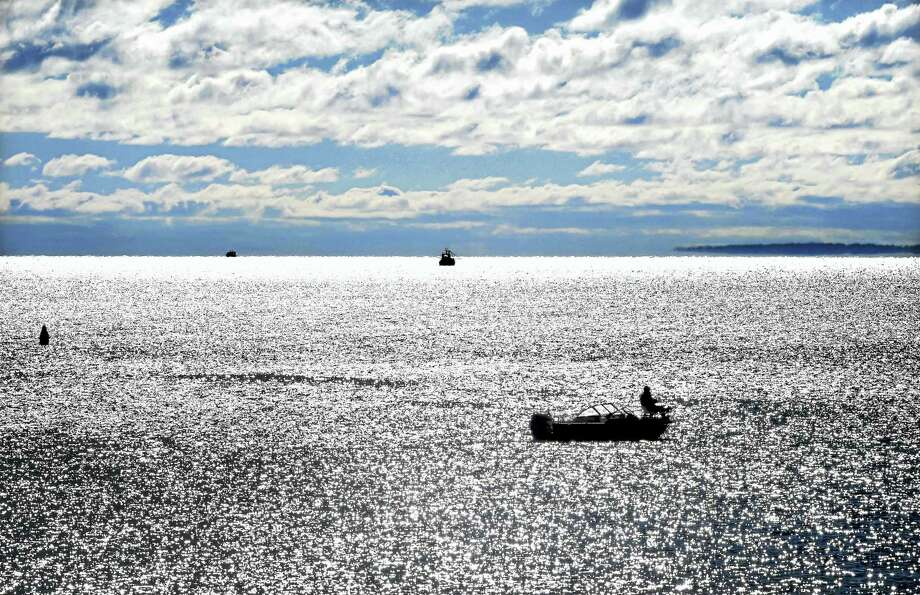 A man fishes in the Long Island Sound in Milford. Photo: Arnold Gold — New Haven Register FILE PHOTO