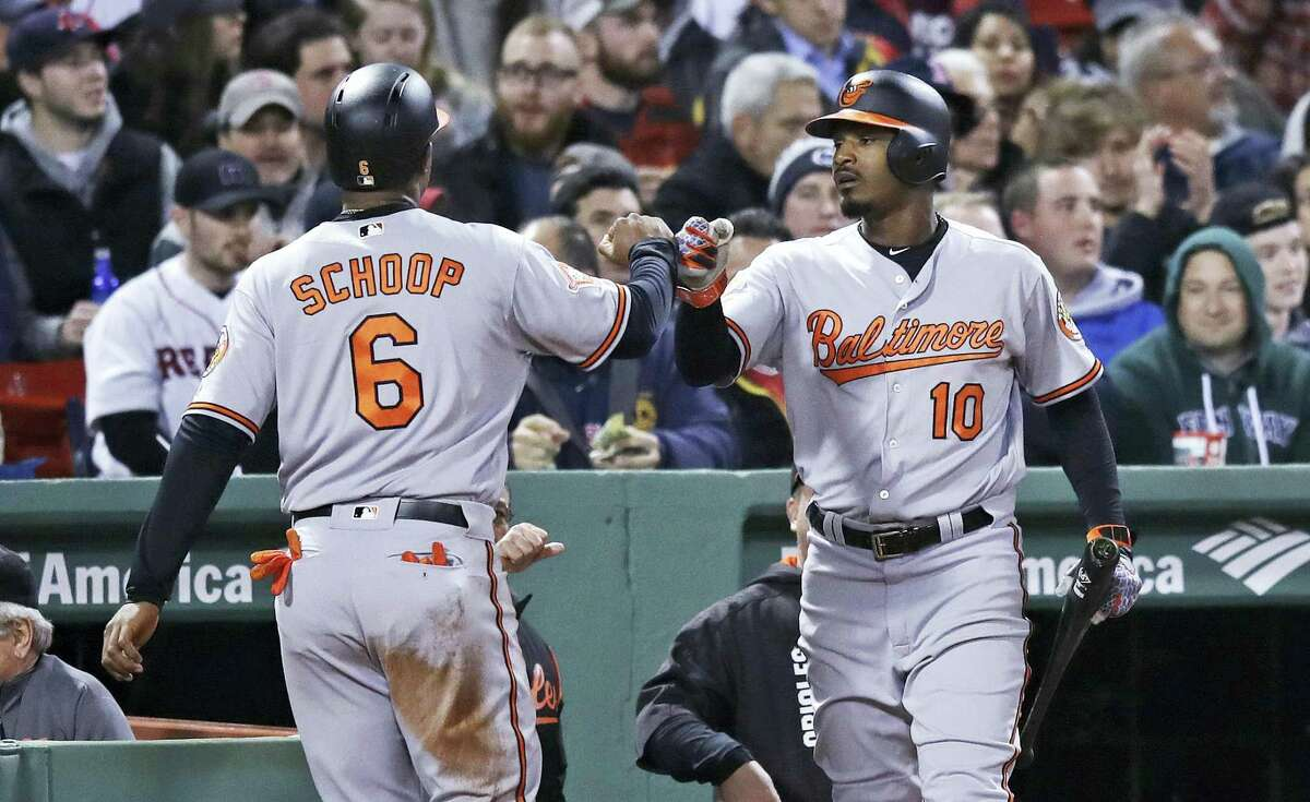 Baltimore Orioles' Jonathan Schoop, left, is congratulated by Adam Jones after scoring on a double by Caleb Joseph during the fifth inning of a baseball game against the Boston Red Sox at Fenway Park in Boston, Monday.